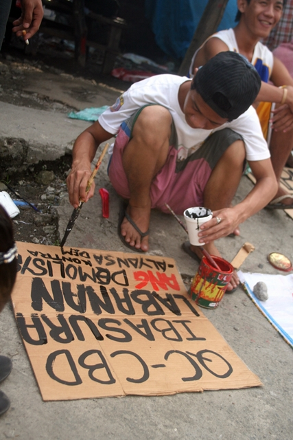 BULATLAT FILE PHOTO: A resident prepares a poster against demolition in sitio San Roque, North Triangle, Quezon City