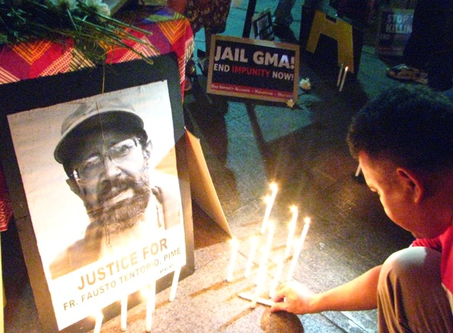 "BULATLAT FILE PHOTO. An activist lights candles in mourning for Italian priest Fausto ""Fr. Pops"" Tentorio who was killed by suspected Alamara paramilitary group in 2011."