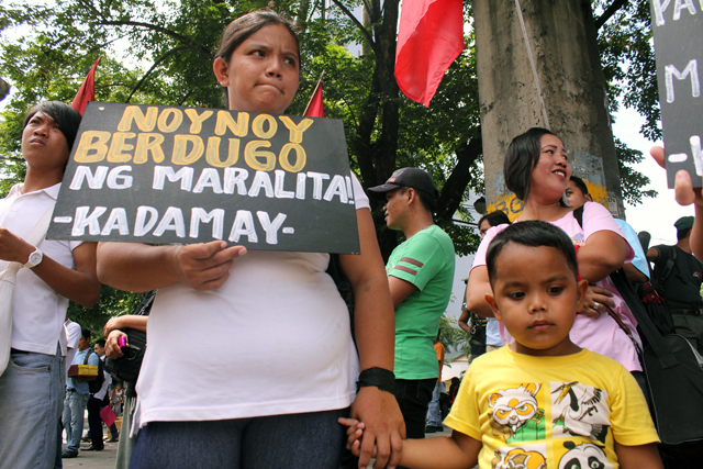 BULATLAT FILE PHOTO: A mother protests with her son over the  violent demolition in Guatemala, Makati City
