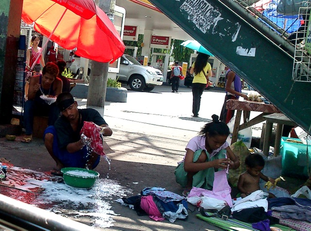 A family feels at home, literally, along Commonwealth avenue in Quezon City. Photo by ANNE MARXZE D. UMIL (Bulatlat.com)