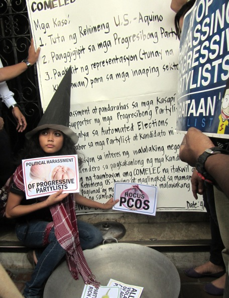 "Progressive groups bring their own ""charges"" to the Comelec Apr 8; a member of Kabataan Partylist demonstrates the magic being cooked up by Comelec"