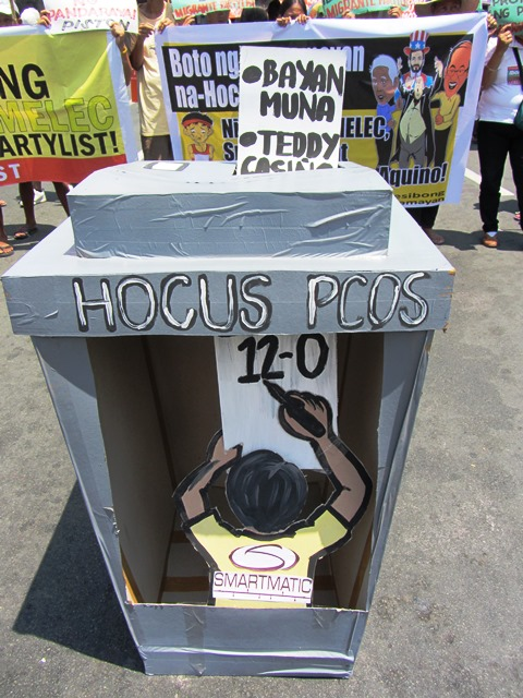 """Bulatlat File Photo: In a May 2013 picket in front of Comelec office in Manila, protesters depict the PCOS machine as instrument where votes are """"magicked,"""" hence, hocus-Pcos"""