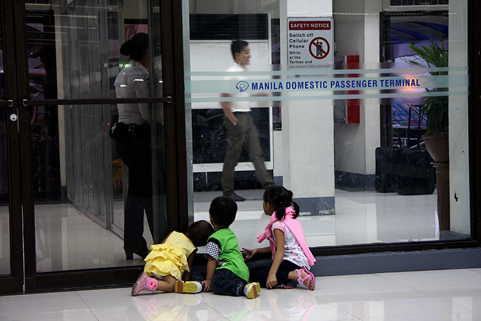 While flights are delayed, arriving planes are diverted, and airport operations are suspended due to a thunderstorm, these toddlers amuse themselves by pretending the airport guard and the airline's ground crews are fishes in an aquarium. (Manila Domestic Airport Terminal)
