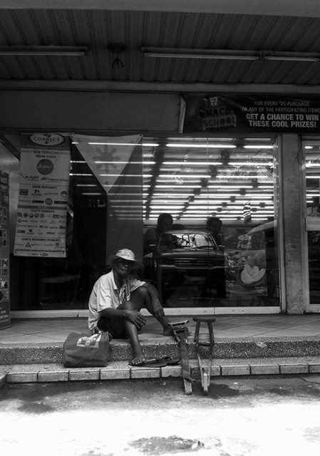 An old beggar takes a rest in front of a multinational convenience store displaying the national flag on the occasion of Philippine Independence Day last June 12.  It was a slow day for him as only a few people were about because of the holiday.  (Matalino Street, Quezon City)