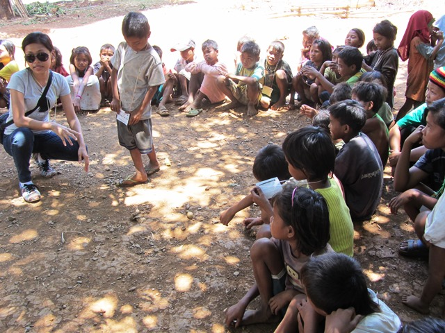 Mangyan children's storytelling under the tree, with IDPIP volunteer (Photo by M. Salamat / Mangyan Day 2013 / www.bulatlat.com)