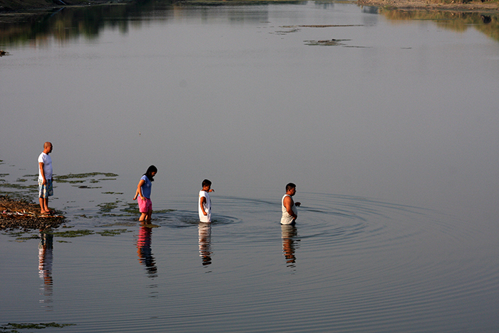 A father leads his two children to the deeper part of a river for an early morning swim, while their host encourages them onward.  (Gapan, Nueva Ecija)