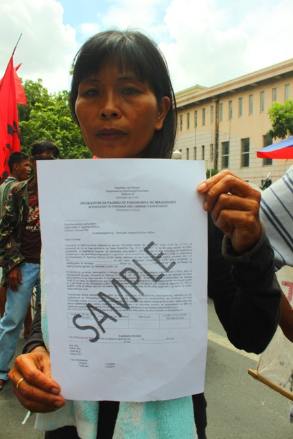 A farm worker shows a copy of the  application to purchase and farmers' undertaking. (Photo by Ronalyn V. Olea / Bulatlat.com)