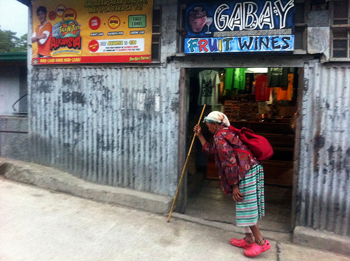 An old Kankanaey lady trudges her way up an incline in this fast-changing town, herself a picture of both the traditional and the contemporary. (Sagada, Mt. Province)