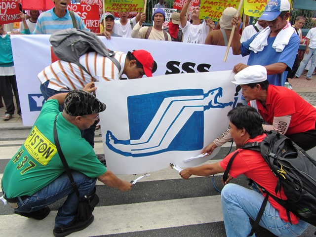Workers ready to burn an image of SSS logo transformed into conjoined snakes