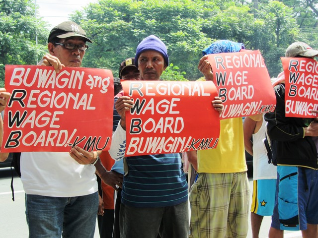 In a picket at the site of final hearing for wage hike petitions in Metro Manila, KMU members tell the board that it is better off  dissolved. They want Congress to legislate a significant wage hike.