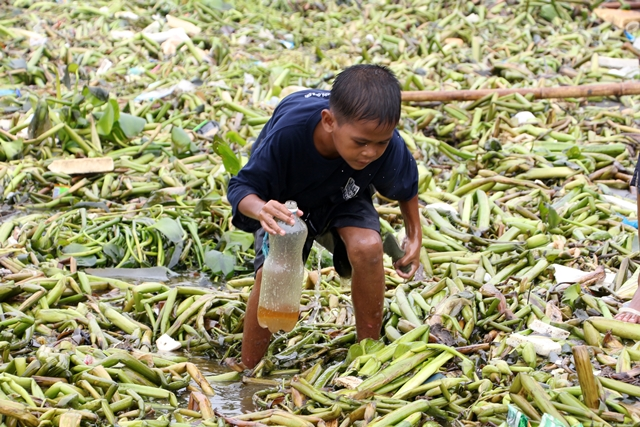 A young boy uses foam to collect oil. (By Jhun Dantes / Bulatlat.com)