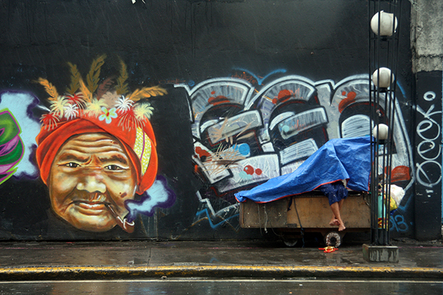 No rosy economic forecast could ever shield society's weakest and most frail from capitalism's exploitative nature.  An abandoned old lady tries to shield herself from the rain, left behind by the Aquino government's so-called economic gains. (Paco, Manila)