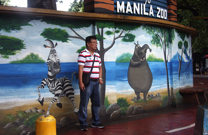 While the mural depicts zoo animals as happy and carefree, this pedestrian's visage is most probably closer to the truth about their caged lives.  (Malate, Manila)