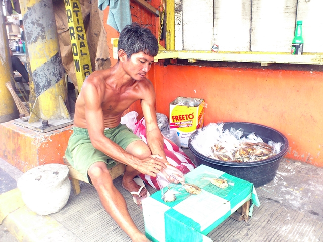 Butch Arcon goes to Manila to sell dried fish because there is no livelihood in relocation site. (Photo by J. Ellao / Bulatlat.com)