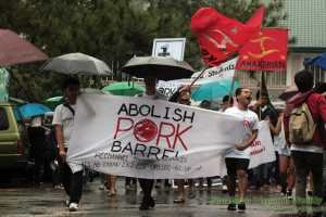 Students from various colleges and universities in Baguio brave the rains and stage a protest action against the pork barrel system, Sept. 20.  (Photo by Noel Godinez/ Northern Dispatch.)