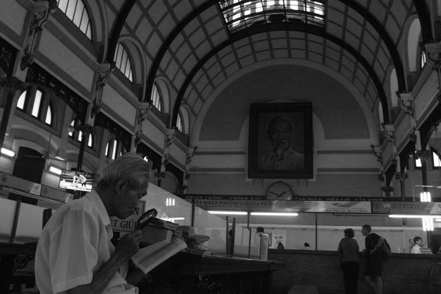 Unmindful of the buzz inside the Post Office, an old man savors every word from his book. (Ho Chi Minh City) (Photo by Ronalyn V. Olea / Bulatlat.com)