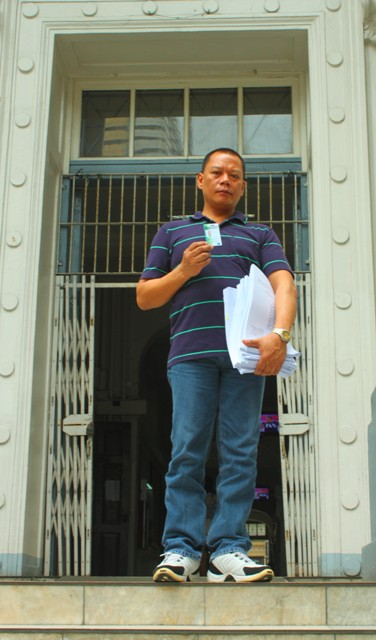 Rolly Mira Panesa steps out of the Department of Justice main building, showing his company ID and a copy of the complaint he filed against his torturers. (Photo by Ronalyn V. Olea/Bulatlat.com)