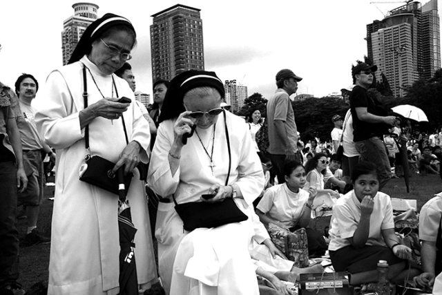 Two Dominican nuns keep up with the times--by texting updates of an anti-corruption rally hundreds of thousands attended.  (Rizal Park, Manila)