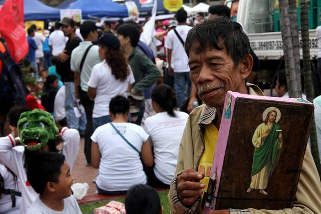 It does not hurt to seek divine help and protection when selling on Manila's streets, on top of a friendly smile.  (Rizal Park, Manila)