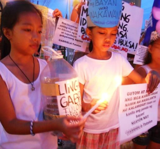 Women's group Gabriela light candles along Araneta, Quezon City (Photo by Anne Marxze D. Umil/Bulatlat.com)