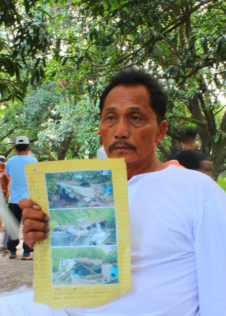 Hector Angeles shows photographs of his hut and pig pen destroyed by the security guards of the LLL Holdings Inc. during a fact-finding mission October 30. (Photo by Ronalyn V. Olea/ Bulatlat.com)