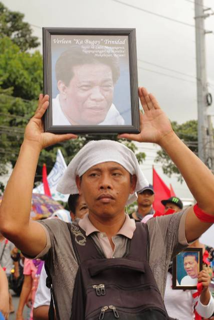 Union president in Asia Brewery holds picture of Verleen Trinidad as he marches with colleagues to Sta. Rosa, Laguna Dec 20, 2013 (Southern Tagalog Exposure photo / bulatlat.com)
