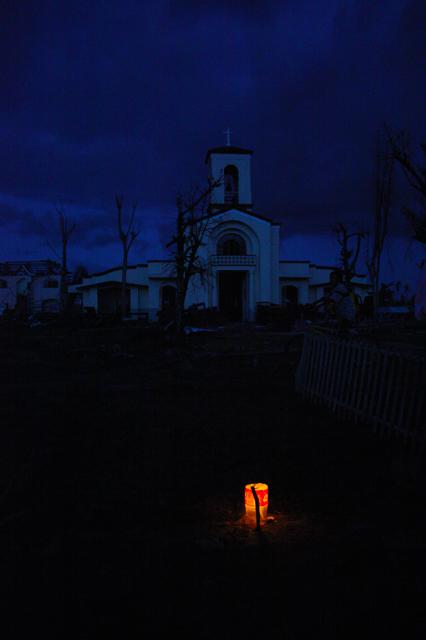 A lit candle on an unmarked grave in San Joaquin Parish, Palo Leyte. (Photo by Pom Cahilog-Villanueva / Bulatlat.com)