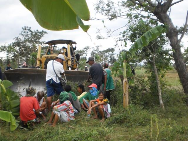 Farmers block a bulldozer from destroying farm lots in Balete village, Hacienda Luisita, Dec. 21. (Photo courtesy of Unyon ng Manggagawa sa Agrikultura)