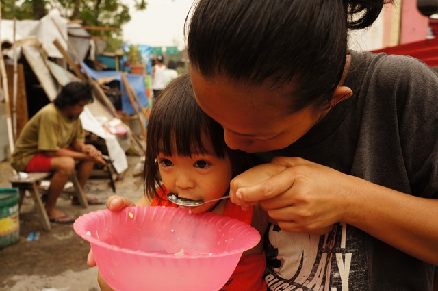 Resident Mildred Bibera and her two-year-old daughter (Photo by J. Ellao / Bulatlat.com)