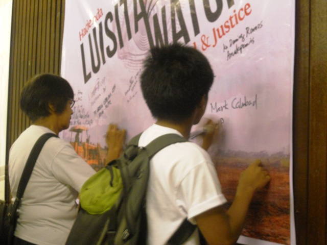 Supporters signing their names in Luisita Watch tarpaulin in solidarity to the Hacienda Luisita farm workers' struggle. (Photo by Anne Marxze D. Umil / Bulatlat.com)