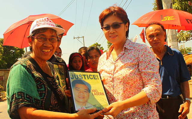 Angie Ipong of Unyon ng Manggagawa sa Agrikultura gives a plaque to Tarlac City Councilor Emily Ladera-Facunla during the commemoration of the death anniversaries of four Hacienda Luisita martyrs, March 13. (Photo by Ronalyn V. Olea/ Bulatlat.com)
