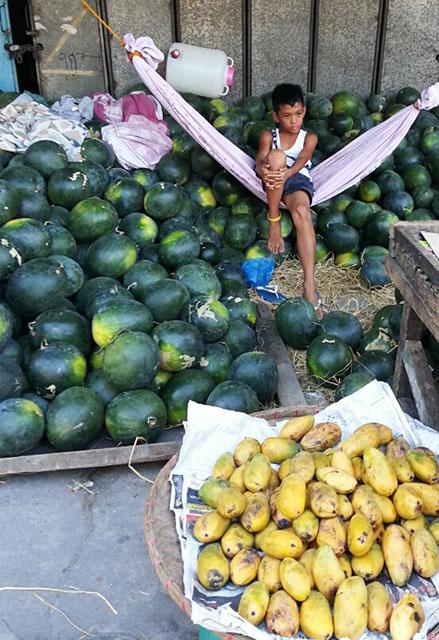 A boy spends his summer selling fruits in season. (San Miguel, Tarlac City) (Photo by Pom Cahilog-Villanueva / Bulatlat.com)