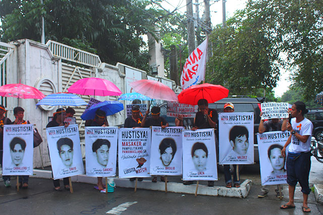 Hacienda Luisita farmers hold tarpaulins bearing the photographs of their seven colleagues killed in the Nov. 16, 2004 massacre outside the Office of the Ombudsman, Aug. 4. (Photo by Ronalyn V. Olea/ Bulatlat.com)