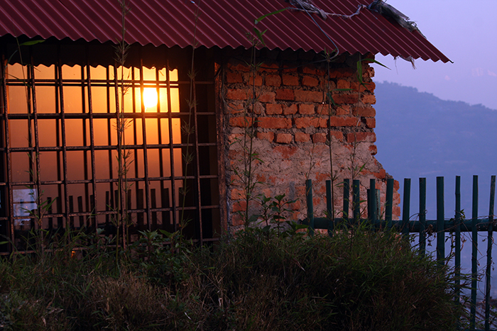 A tinted window shows its interpretation of the rising sun's colors.  (Outlook Hotel, Nepal)