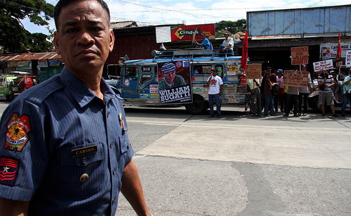 This police officer tried to prevent the photojournalist from taking photos of a public event with him in included in the frame.  The shutter button was pressed anyway as he was presumed to be on duty because of his uniform.  Many PNP personnel are camera shy when they have nothing to report on the status of investigations, such as the extrajudicial killing of Bayan Muna provincial coordinator William Bugatti.  (Lamut, Ifugao)