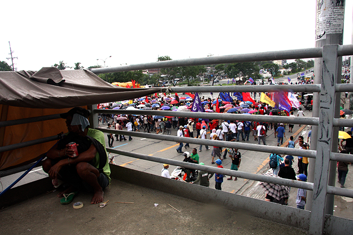 A homeless person watches protesters marching towards the Philippine House of Representatives.  In their speeches, the activists point to the high incidence of poverty in the country as one of the reasons for their activism. (Commonwealth Avenue, Quezon City)