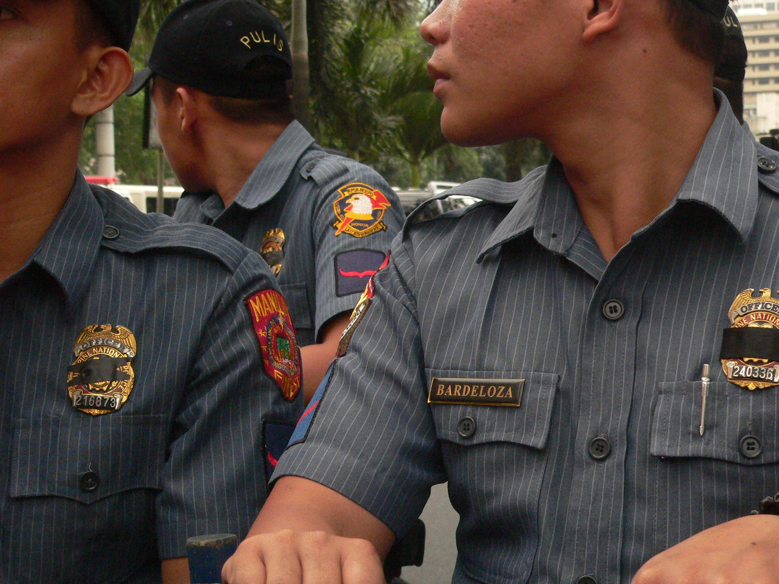 Anti-riot police men wear black ribbon over their badges (Photo by D.Ayroso)
