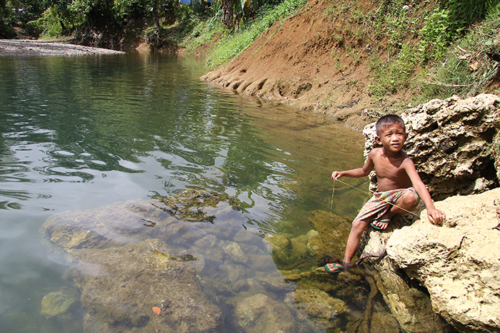 A tyke is line fishing in a crystal-clear brook that runs through his village.  Such spots and activities are denied urban born and raised kids nowadays. (Hernani, Eastern Samar)