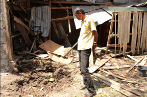 Alon Maytula looks at the crater and his wrecked home pounded by mortar shells. (Photo by Kilab Multimedia)