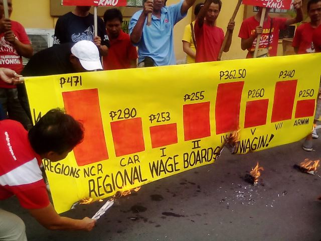 Chart depicting varying levels of paltry minimum wages burned in front of labor department by members of KMU March 23