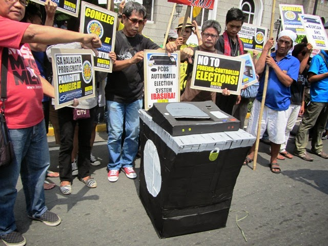Bulatlat FILE PHOTO: Protesters in front of Comelec headquarters  in Manila denounce the 'hocu-pocus' of PCOS machines (June 2013 /  Bulatlat.com)
