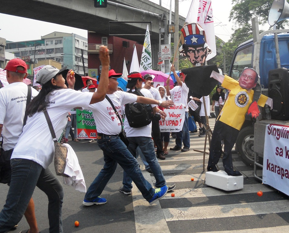 Health workers show their rage by throwing tomatoes at the effigies of President Aquino and the Uncle Sam for implementing anti-people policies like privatization. (Photo by A. Umil/ Bulatlat.com)