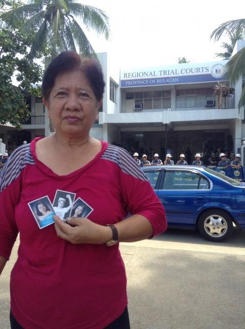 Mrs. Empeno holds photos of daughter Karen. (Photo by J. Ellao / Bulatlat.com)