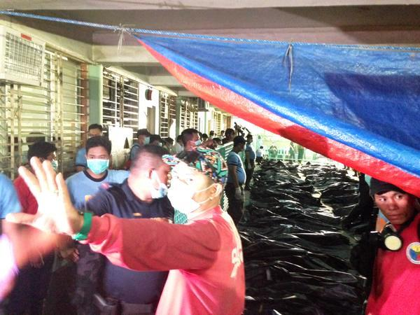Bodies of 69 Valenzuela fire victims laid in rows for strictly-for-families viewing. (Photo by Tudla Productions, May 14, 2015)