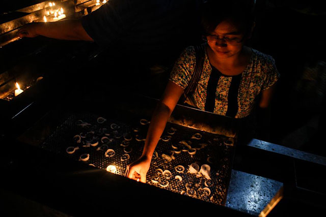 A member of Talents Association of GMA (TAG) lights a candle at the Sacred Heart Parish, June 3. (Photo by Manila Today)