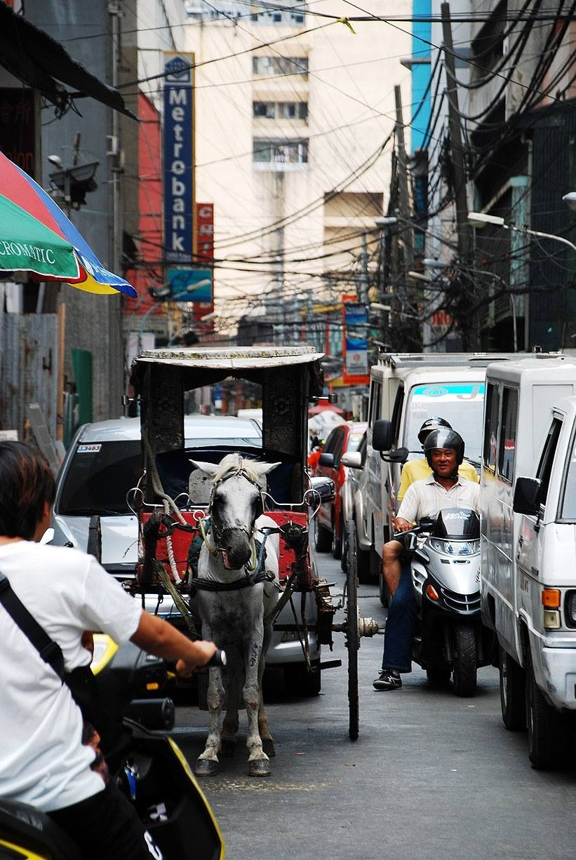 A 'karwaje' gets tangled in traffic among modern modes of transportation in Chinatown, Binondo. (Photo by Cong Corrales / Bulatlat.com)