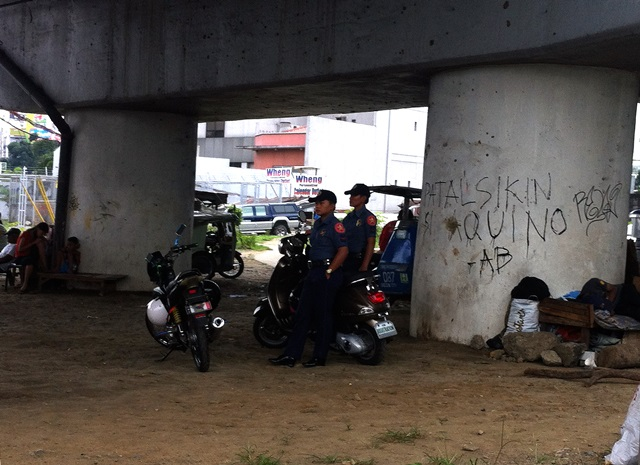 Police officers seek shelter from the heat of the noonday sun under a bridge, unmindful of the writing on the wall. (Commonwealth Avenue, Quezon City)
