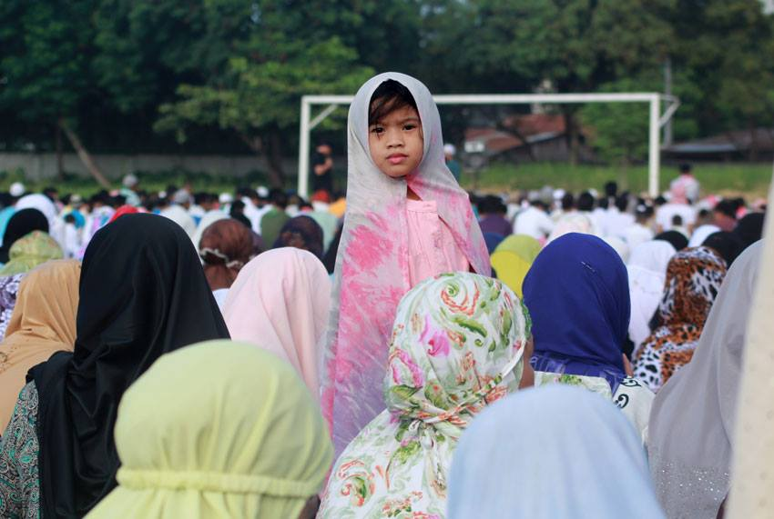 A Muslim child watches around the field, while elder Muslims listen to the preaching of their Imam during the celebration of the Eid'l Fitr on Friday at Tionko Football Field in Davao City.