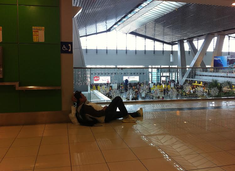 A passenger whiles the time away by catching a wink while waiting for his delayed flight.  (NAIA, Parañaque City)