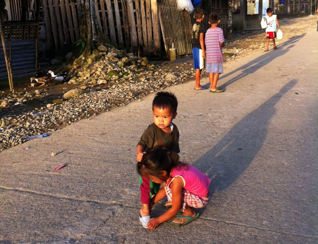 A young girl plays big sister to a younger brother as they take an early morning walk on their community's main street.  (General McArthur, Leyte)